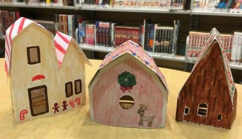Three paper houses decorated with markers and colored pencils