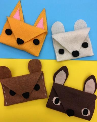 Four felt pouches: dark yellow fox, white polar bear, brown deer, and brown squirrel
