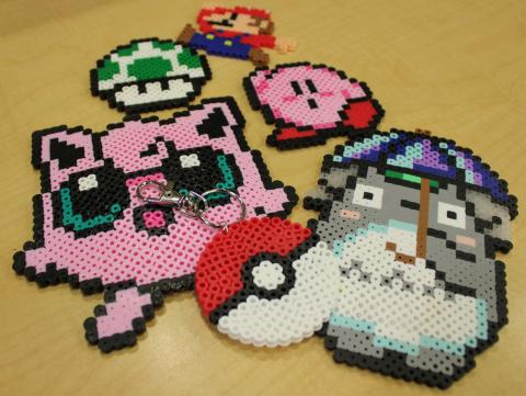 pixel art examples made out of perler beads: Jigglypuff, Totoro, Kirby, Mario, and a mushroom and poke ball