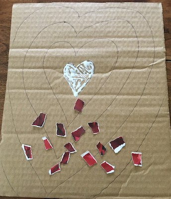 Small heart of glue with small pieces of torn red magazine pieces
