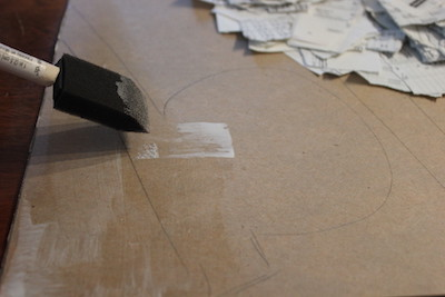 Foam brush spreading glue in a thin layer onto cardboard backing