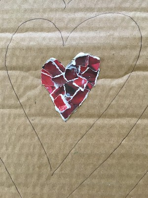Red heart made of torn up pieces of magazine