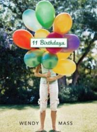 Cover of 11 Birthdays; a large bunch of balloons held in front of a girl's face