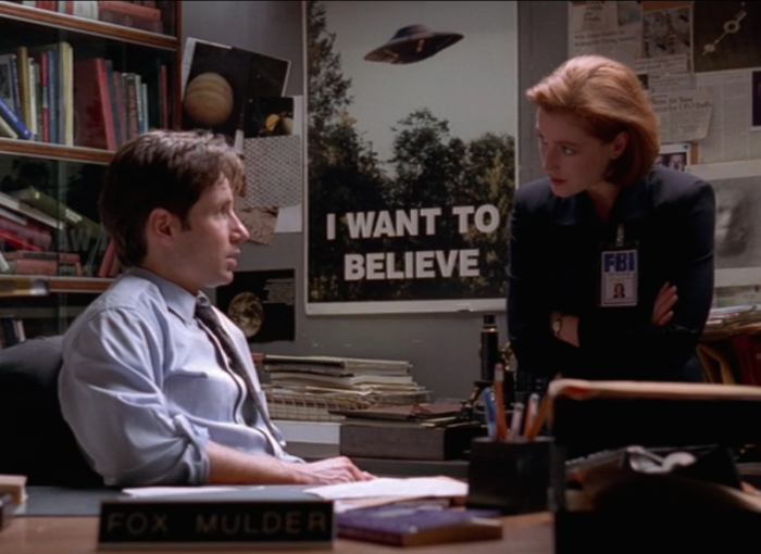 two FBI agents sit at a desk in front of a poster reading I Want to Believe