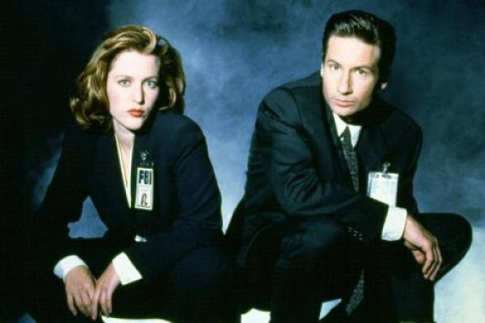 a female FBI agent (Scully) crouching next to a crouching male FBI agent (Mulder)